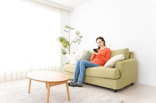 家でスマホを使う若い女性の写真素材 [FYI04712086]