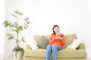 家でスマホを使う若い女性の写真素材 [FYI04712089]
