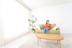 家でスマホを使う若い女性の写真素材 [FYI04712097]