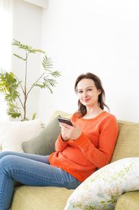 家でスマホを使う若い女性の写真素材 [FYI04712115]