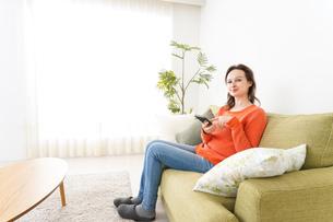 家でスマホを使う若い女性の写真素材 [FYI04712117]