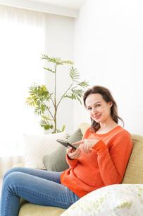家でスマホを使う若い女性の写真素材 [FYI04712119]
