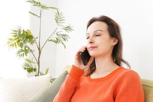 家で通話をする若い女性の写真素材 [FYI04712122]