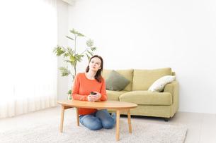 家でコーヒーを飲む若い女性の写真素材 [FYI04712134]