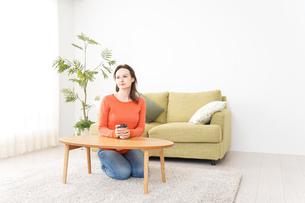 家でコーヒーを飲む若い女性の写真素材 [FYI04712135]