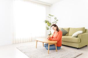 家でコーヒーを飲む若い女性の写真素材 [FYI04712142]