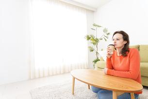 家でコーヒーを飲む若い女性の写真素材 [FYI04712144]