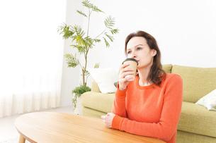 家でコーヒーを飲む若い女性の写真素材 [FYI04712146]