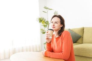 家でコーヒーを飲む若い女性の写真素材 [FYI04712148]
