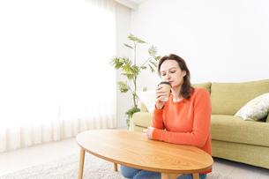 家でコーヒーを飲む若い女性の写真素材 [FYI04712149]