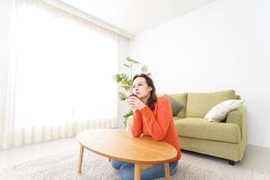 家でコーヒーを飲む若い女性の写真素材 [FYI04712161]