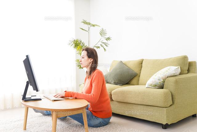 自宅でパソコンを使う若い女性の写真素材 [FYI04712188]