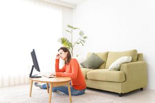 自宅でパソコンを使う若い女性の写真素材 [FYI04712192]
