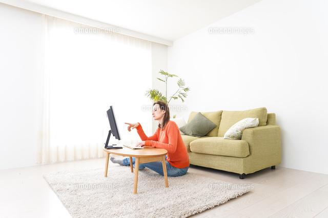 自宅でパソコンを使う若い女性の写真素材 [FYI04712196]