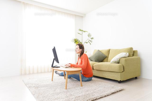 自宅でパソコンを使う若い女性の写真素材 [FYI04712197]