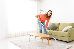 家を掃除する若い女性の写真素材 [FYI04712198]