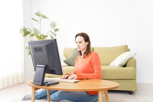 自宅でパソコンを使う若い女性の写真素材 [FYI04712202]