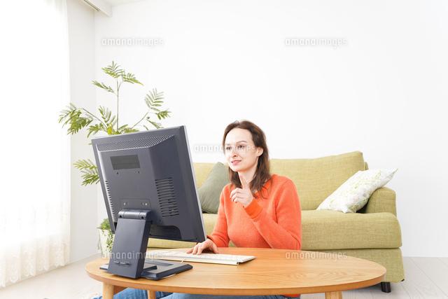 自宅でパソコンを使う若い女性の写真素材 [FYI04712205]