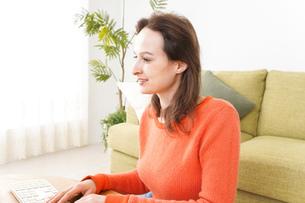 自宅でパソコンを使う若い女性の写真素材 [FYI04712210]