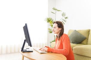 自宅でパソコンを使う若い女性の写真素材 [FYI04712211]