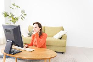 自宅でパソコンを使う若い女性の写真素材 [FYI04712213]