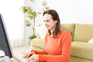 自宅でパソコンを使う若い女性の写真素材 [FYI04712215]