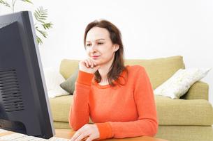 自宅でパソコンを使う若い女性の写真素材 [FYI04712216]