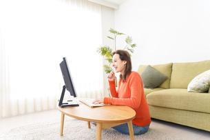 自宅でパソコンを使う若い女性の写真素材 [FYI04712218]