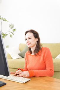 自宅でパソコンを使う若い女性の写真素材 [FYI04712220]