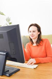 自宅でパソコンを使う若い女性の写真素材 [FYI04712221]