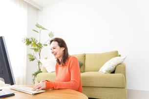 自宅でパソコンを使う若い女性の写真素材 [FYI04712223]