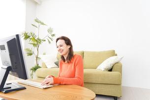 自宅でパソコンを使う若い女性の写真素材 [FYI04712224]