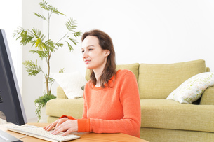 自宅でパソコンを使う若い女性の写真素材 [FYI04712225]