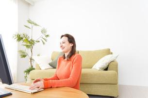 自宅でパソコンを使う若い女性の写真素材 [FYI04712226]