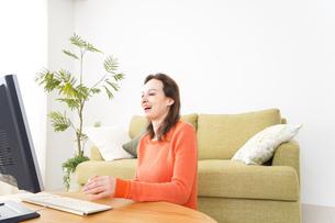 自宅でパソコンを使う若い女性の写真素材 [FYI04712227]