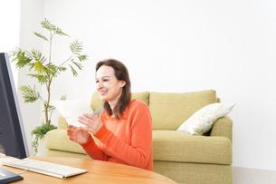 自宅でパソコンを使う若い女性の写真素材 [FYI04712228]