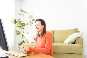 自宅でパソコンを使う若い女性の写真素材 [FYI04712230]