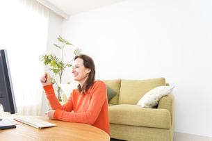 自宅でパソコンを使う若い女性の写真素材 [FYI04712231]