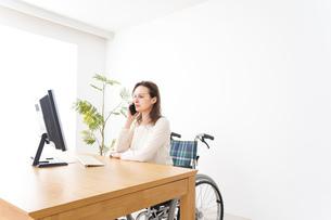 車椅子でデスクワークをする外国人の女性の写真素材 [FYI04712331]