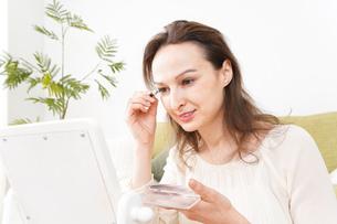 自宅で化粧をする若い女性の写真素材 [FYI04712333]
