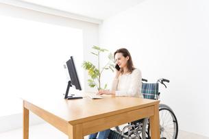 車椅子でデスクワークをする外国人の女性の写真素材 [FYI04712336]