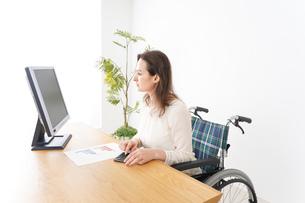 車椅子でデスクワークをする外国人の女性の写真素材 [FYI04712340]