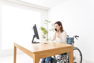 車椅子でデスクワークをする外国人の女性の写真素材 [FYI04712344]