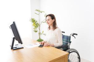 車椅子でデスクワークをする外国人の女性の写真素材 [FYI04712346]