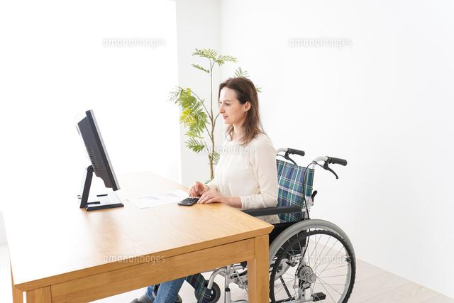 車椅子でデスクワークをする外国人の女性の写真素材 [FYI04712353]