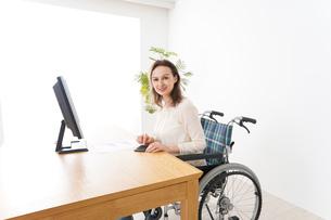 車椅子でデスクワークをする外国人の女性の写真素材 [FYI04712354]