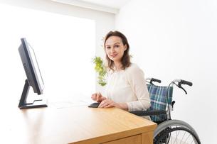 車椅子でデスクワークをする外国人の女性の写真素材 [FYI04712355]