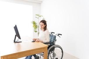 車椅子でデスクワークをする外国人の女性の写真素材 [FYI04712358]