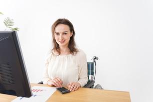 車椅子でデスクワークをする外国人の女性の写真素材 [FYI04712365]