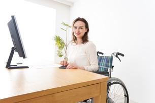 車椅子でデスクワークをする外国人の女性の写真素材 [FYI04712366]
